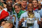 Mario Balotelli, Roberto Mancini and Vincent Kompany celebrate Man City's first title win for 44 years.