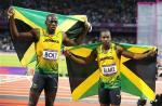 Usain Bolt celebrates his 100m victory with silver medalist Yohan Blake.